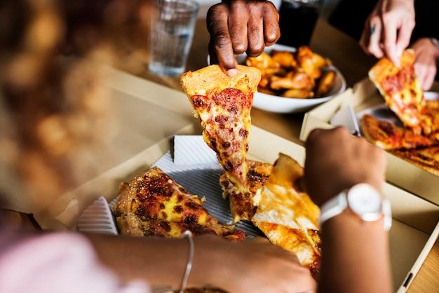 Freunde, die zusammen zu hause pizza essen