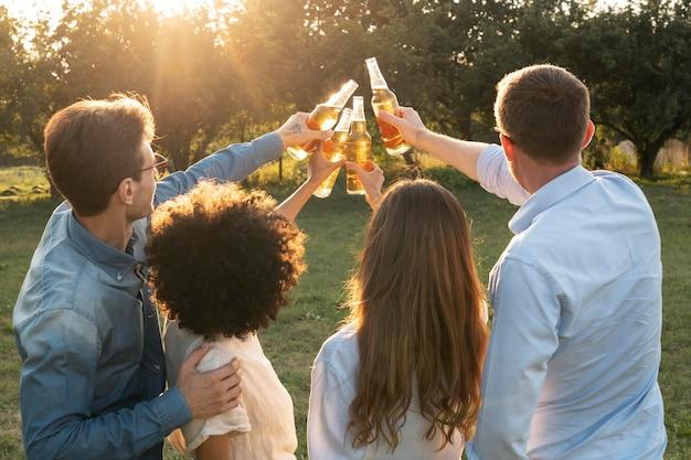 Freunde draußen im park, die zusammen bier trinken