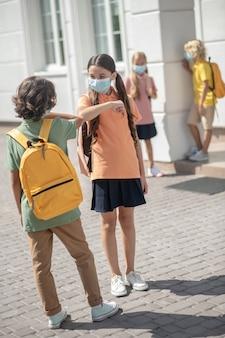 Freunde. ein junge und ein mädchen in masken begrüßen sich auf einem schulhof