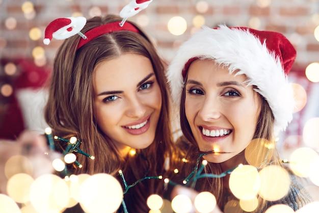 Freunde eingewickelt in weihnachtslichter posierend