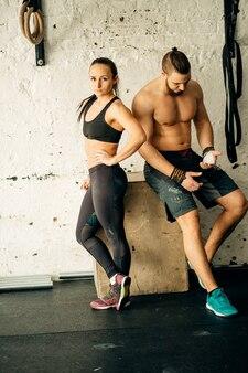 Freunde entspannen sich und machen eine pause, nachdem sie in einem cross-training-fitnessstudio trainiert haben