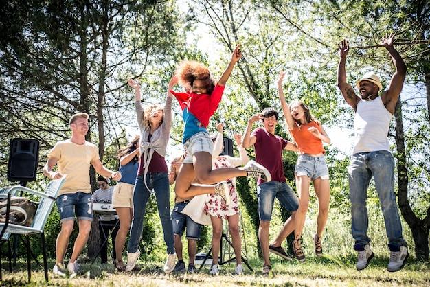 Freunde essen beim picknick. party machen und in der natur tanzen