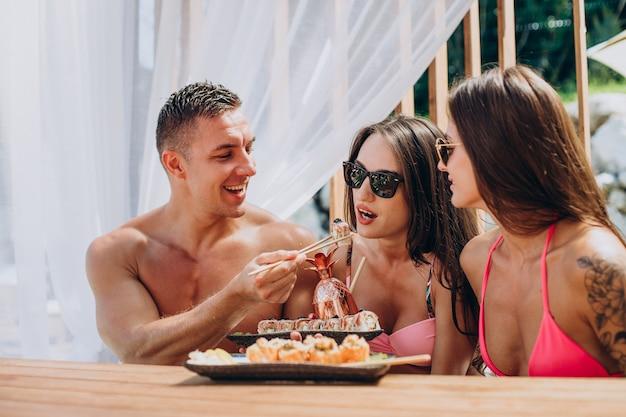 Freunde essen zusammen sushi-rollen am pool