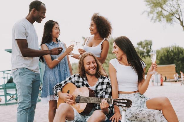Freunde feiern am strand gitarre spielen.