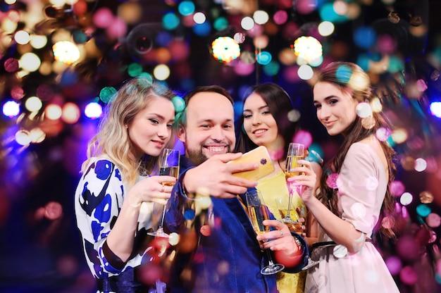 Freunde feiern die veranstaltung, lachen, tanzen und trinken champagner