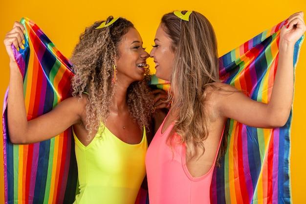 Freunde frauen im kostüm genießen die karnevalsparty, die mit lgbt stolzflagge bedeckt. paar. zwei. faust hochhalten, lgbt-flagge abdecken. lgbt + flagge an der gelben wand.