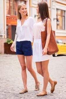 Freunde gehen zusammen. zwei schöne junge frauen, die zusammen die straße entlang gehen und lächeln