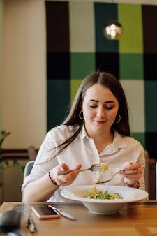 Freunde genießen das mittagessen im restaurant und essen paste