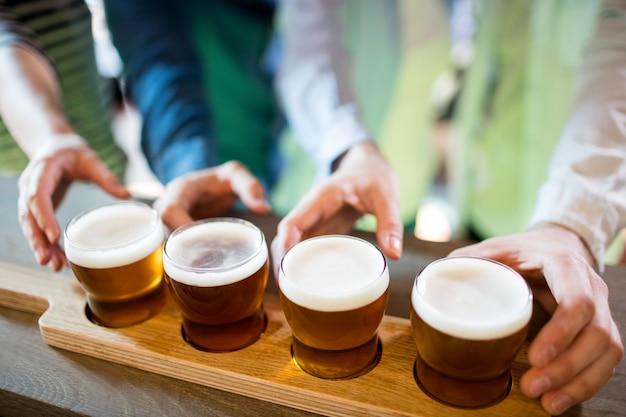 Freunde greifen nach bierproben auf der theke