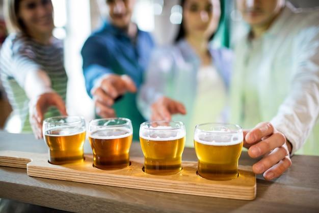 Freunde greifen nach bierproben