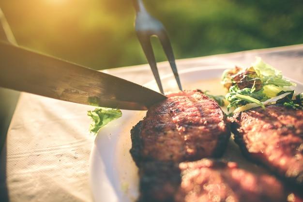 Freunde grillen und in der natur zu mittag essen. paare, die spaß beim essen und trinken an einem picknick haben - glückliche leute an der grillparty.