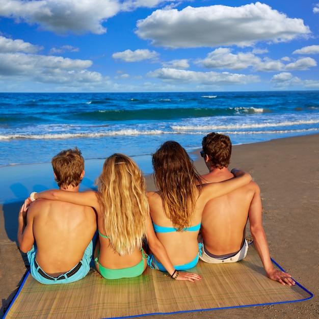 Freunde gruppe paare im hinteren strand sand sitzen