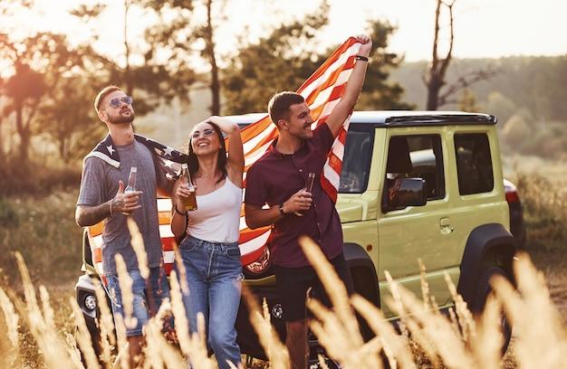 Freunde haben ein schönes wochenende im freien in der nähe ihres grünen autos mit der usa-flagge