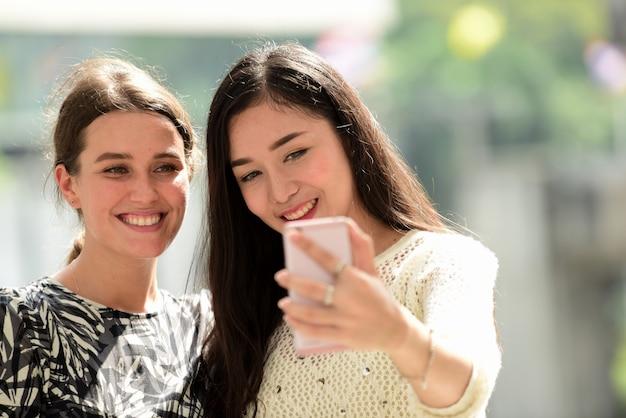 Freunde haben fotos mit mobiltelefonen gemacht. am treffpunkt in der stadt.