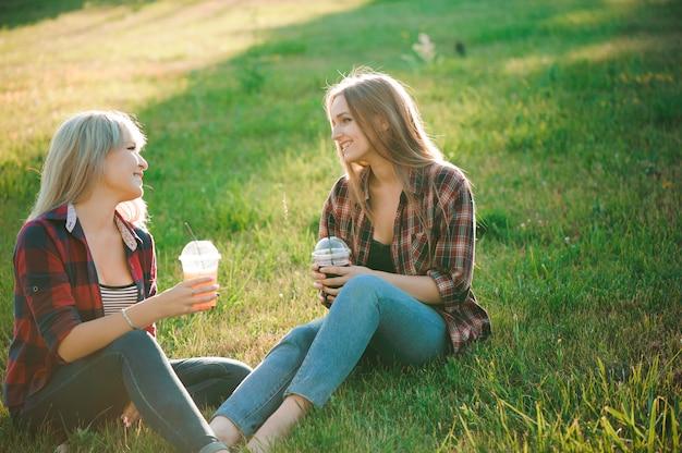 Freunde haben spaß im park und trinken smoothies bei einem picknick.