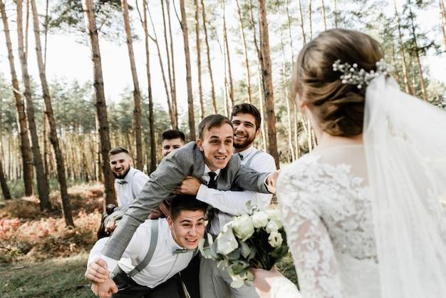 Freunde halten einen lustigen bräutigam in den armen, der die braut um einen kuss bittet