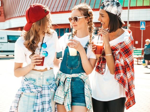 Freunde halten und trinken frisches cocktail-smoothie-getränk im plastikbecher mit strohhalm