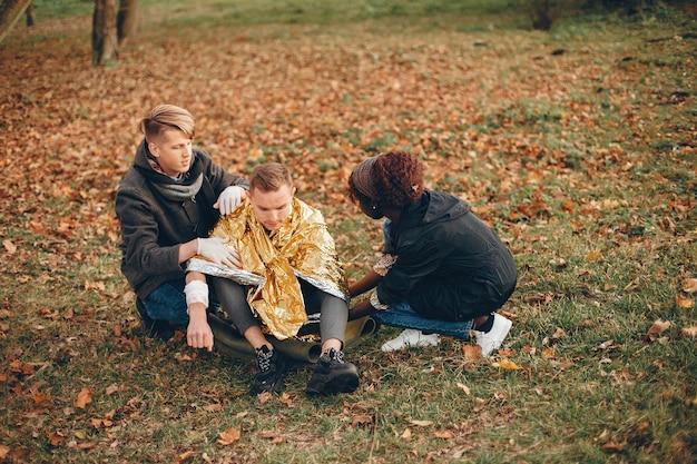Freunde helfen dem kerl. der verwundete junge sitzt auf dem boden. erste hilfe im park leisten.