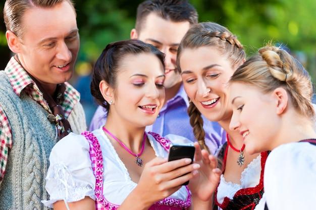 Freunde im biergarten mit smartphone
