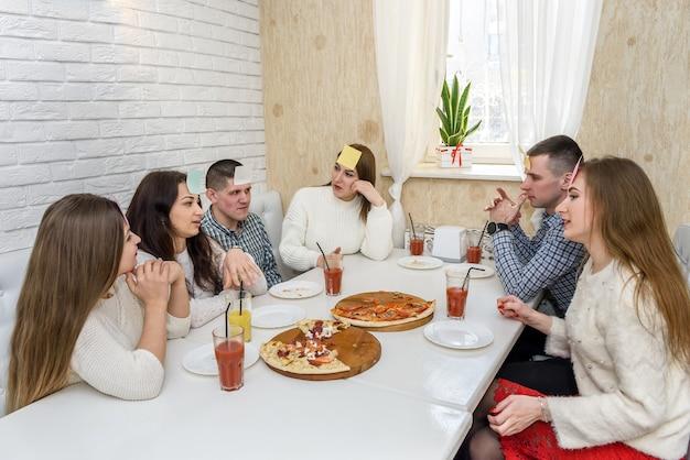 Freunde im café essen pizza und posieren für die kamera
