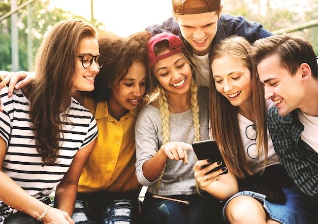 Freunde im park, der unter verwendung des tausendjährigen und jugendkulturkonzeptes der smartphones schaut