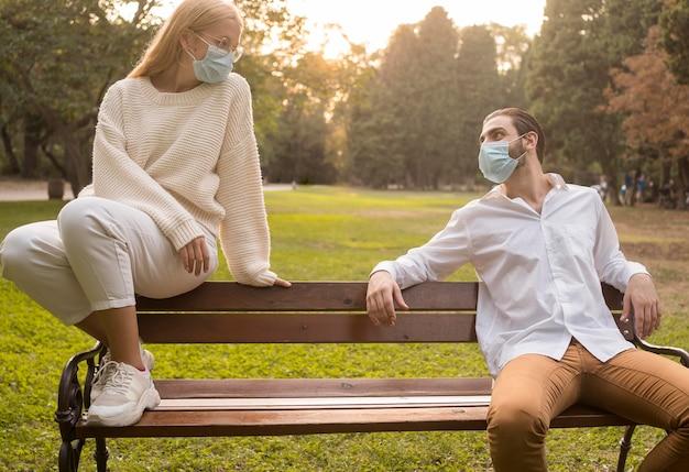 Freunde im park mit medizinischen masken, die soziale distanz üben