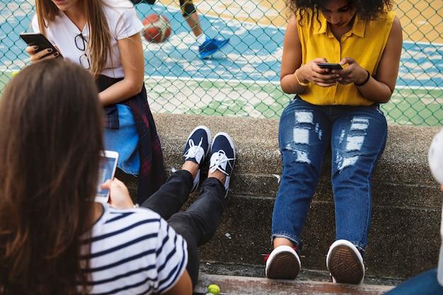 Freunde im park unter verwendung der smartphones