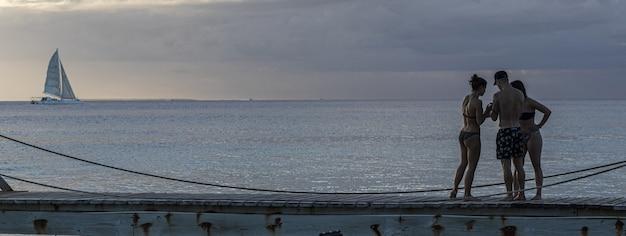Freunde im urlaub am pier bei sonnenuntergang, bannerbild mit kopienraum