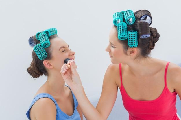 Freunde in den haarrollen, die spaß mit make-up haben