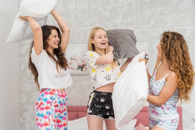 Freunde in der pijama-partei, die mit kissen kämpft