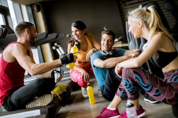 Freunde in der sportkleidung zusammen sprechend bei der stellung in einer turnhalle nach einem training