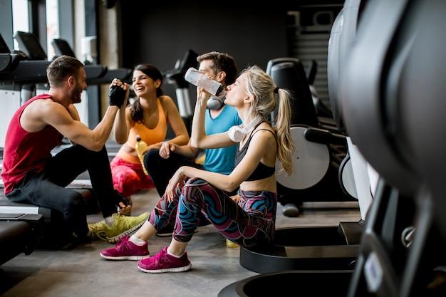 Freunde in der sportkleidung zusammen sprechend und beim sitzen lachend auf dem boden einer turnhalle nach einem training