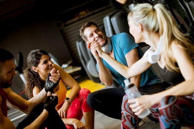 Freunde in der sportkleidung zusammen sprechend und lachend beim stillstehen in der turnhalle nach einem training