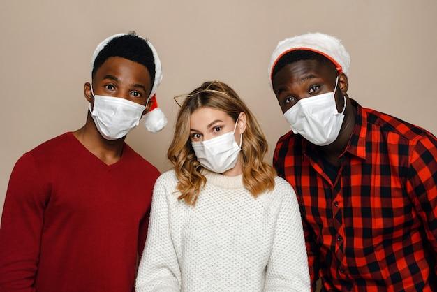 Freunde in der weihnachtsmütze und in den medizinischen masken, die zusammen aufwerfen