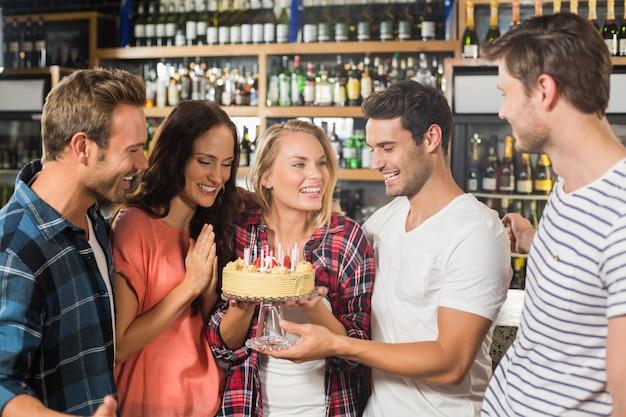 Freunde in einem kreis, der einen kuchen hält