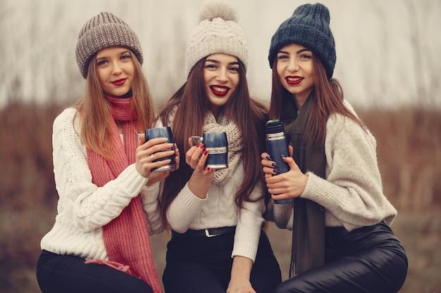 Freunde in einem winterpark. mädchen in strickmützen. frauen mit thermoskanne und tee.