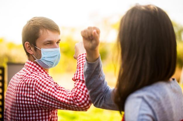 Freunde in einer schützenden medizinischen maske auf seinem gesicht begrüßen ihre ellbogen in quarantäne. ellenbogenbeule. coronavirus, krankheit, quarantäne, medizinische maske, covid19. paar gruß mit ellbogen. ellbogen stoßen.