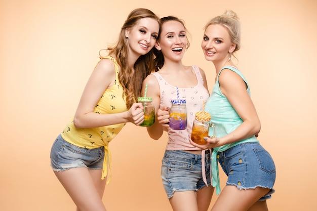 Freunde in freizeitkleidung trinken limonade während der ferien.
