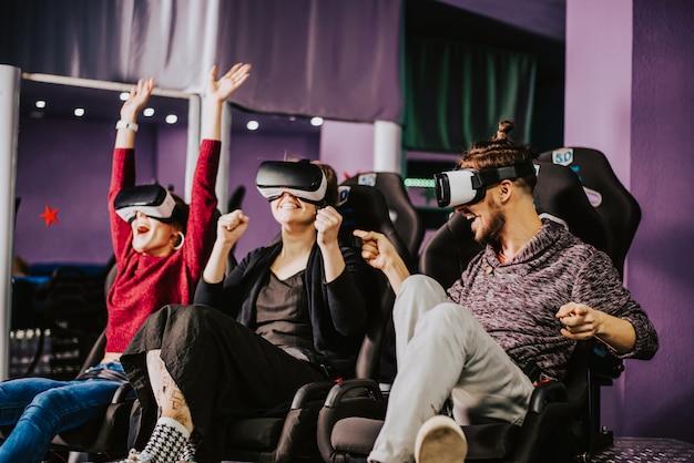 Freunde in virtuellen gläsern schauen sich filme im kino mit spezialeffekten in 5d an