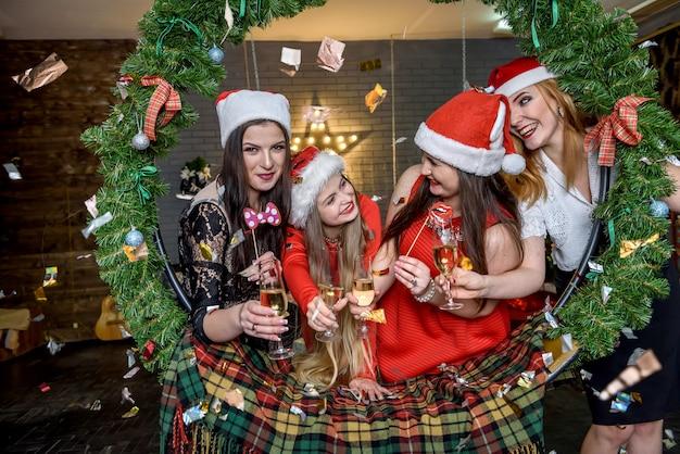 Freunde in weihnachtsmützen posieren im weihnachtsstudio