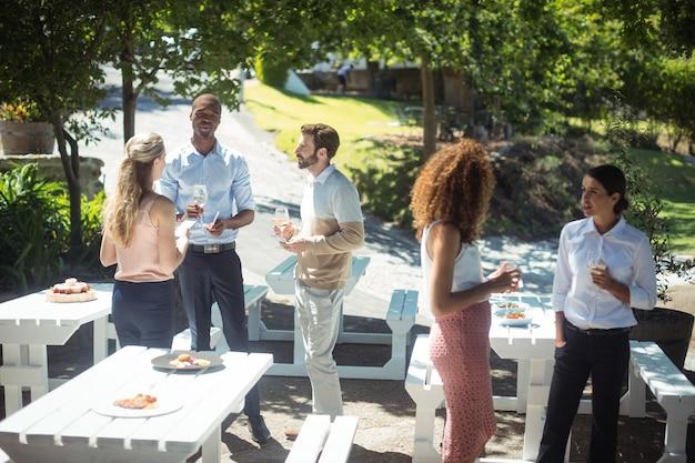 Freunde interagieren, während sie ein glas wein im restaurant trinken