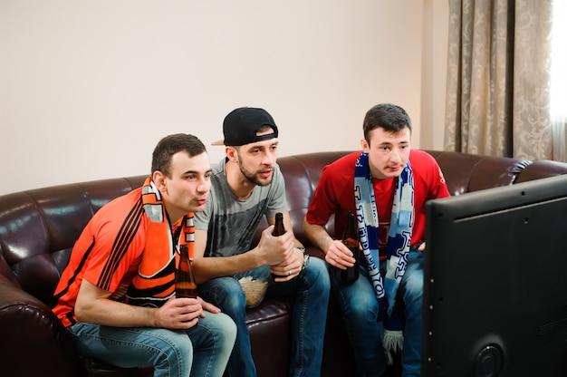 Freunde jubeln und trinken alkohol, während sie fußballspiel im fernsehen sehen.