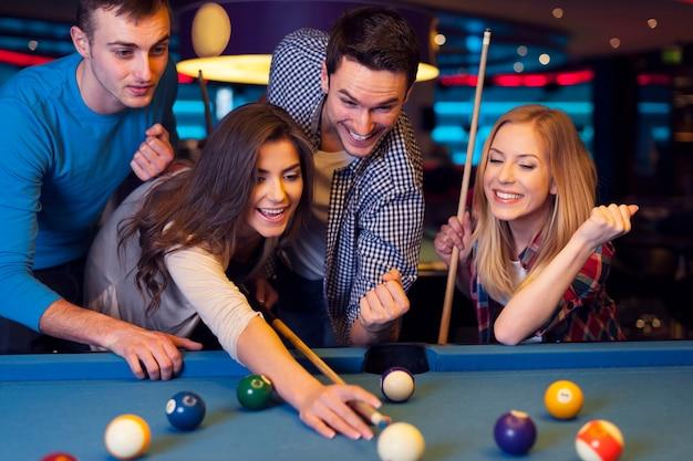 Freunde jubeln, während ihr freund auf billardball zielt