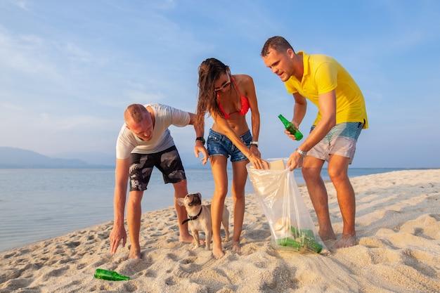 Freunde junger leute, die müll und müll auf tropischem strand aufheben, der planeten und ökologie in indonesien, thailand und den philippinen rettet