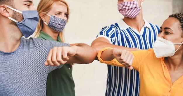 Freunde junger leute stoßen mit den armen, anstatt sie mit einer umarmung zu begrüßen. - vermeiden sie die verbreitung von coronavirus, sozialer distanz und freundschaftskonzept. - konzentrieren sie sich auf nahaufnahmen
