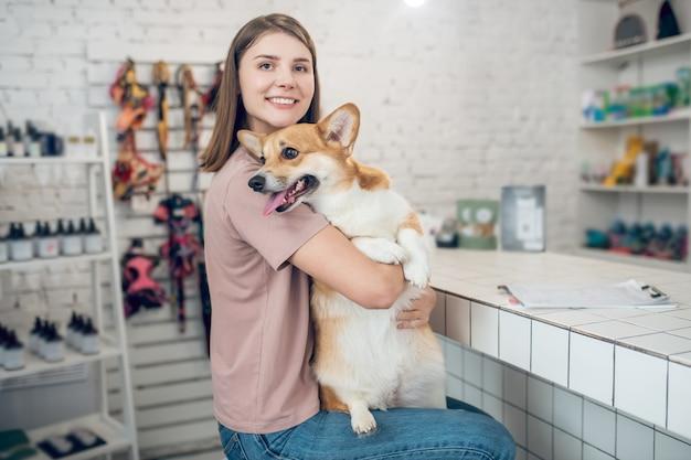 Freunde. junger weiblicher haustierbesitzer, der ihren hund hält und sich glücklich fühlt