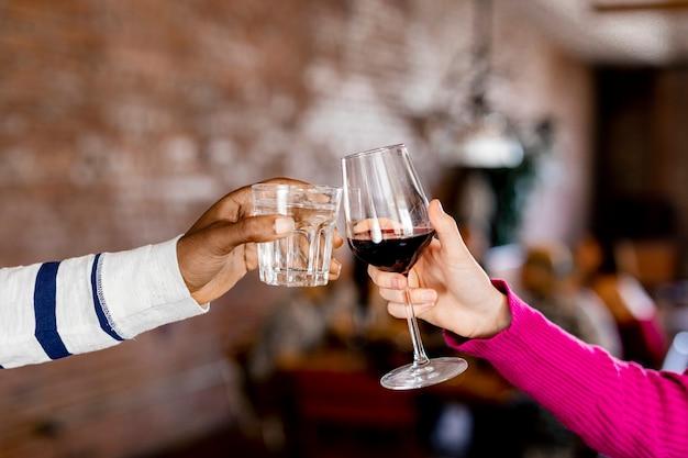 Freunde klirren bei einer dinnerparty mit den gläsern