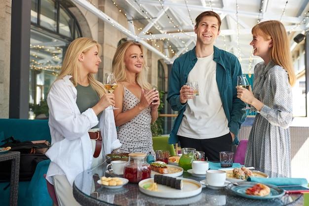 Freunde klirren gläser über esstisch im restaurant