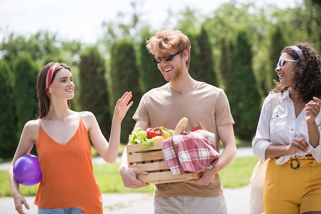 Freunde, kommunikation. fröhliche junge wohlhabende leute, die sich an einem warmen sonnigen tag im park beim picknick ausruhen