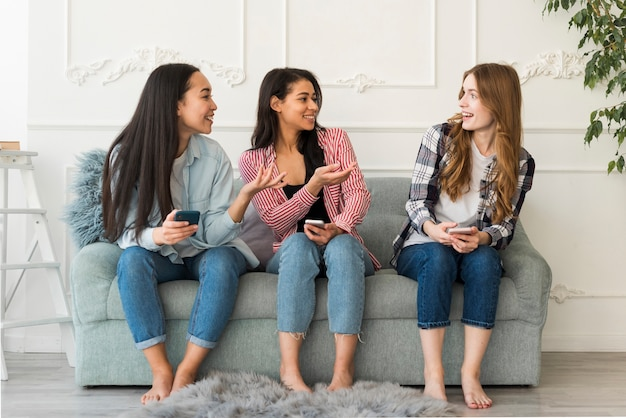 Freunde kommunizieren auf der couch sitzen